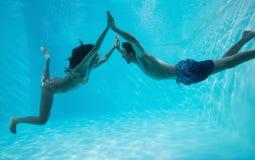 Paarholding handen en zwemmen onderwater Stock Foto