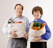 Paarholding-Lebensmittelgeschäftbeutel voll der Frucht Stockbild
