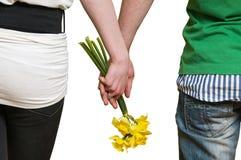 Paarholdingblumen in den Händen Lizenzfreie Stockfotos