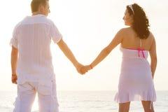 Paarholdinghände zusammen auf dem Strand Lizenzfreie Stockfotos