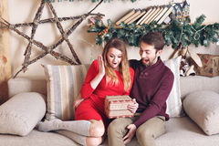 Paarliebe im Schock Glückliches lächelndes und wunderndes auspackendes Weihnachtsgeschenk von ihrem hübschen Freund, Gutschein Stockbild