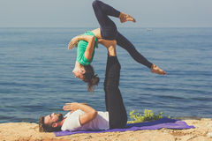 Paarmädchen und -junge üben acroyoga auf Lizenzfreies Stockfoto