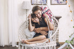 Paarman en vrouw in een het hangen stoel geknuffel stock afbeeldingen