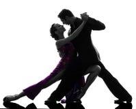 Paarmannfrauen-Ballsaaltänzer, die Schattenbild tangoing sind stockfoto