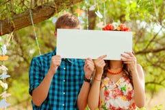 Paarmeisje en mens met wit teken in zijn handen Stock Foto's