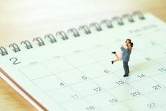 Paarminiatur2 menschen, die auf Kalender stehen Tag 14 trifft Val Stockbild