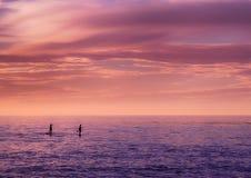 Paarpeddel die bij zonsondergang inscheept Stock Fotografie