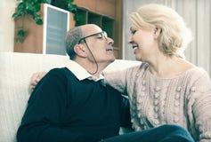 Paarpensionäre zusammen auf Sofa zu Hause Lizenzfreie Stockbilder