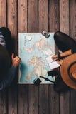 Paarplanungsferien, die durch die Weltkarte sitzen Stockfotografie