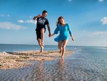 Paarpret op strand Romantische Mensen in Liefde die op Zand bij Luxe Overzeese Toevlucht lopen Knappe Gelukkige Man, Mooie Glimla stock afbeelding