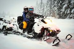Paarschneemobile im Schneesturm Stockbilder