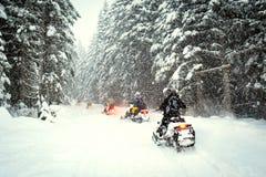 Paarschneemobile im Schneesturm Stockfotografie