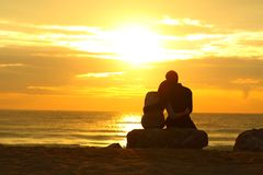 Paarsilhouet die bij zonsondergang op het strand dateren royalty-vrije stock afbeeldingen