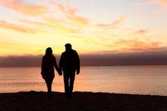 Paarsilhouetten die samen bij zonsondergang lopen stock afbeeldingen