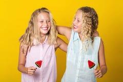 Paart Mädchen mit der bunten Süßigkeit, die Spaß zusammen hat, lokalisiert auf dem gelben Hintergrund stockfotos
