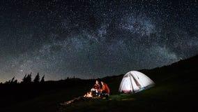 Paartoeristen dichtbij kampvuur en tenten onder het hoogtepunt van de nachthemel van sterren en melkachtige manier Royalty-vrije Stock Foto's