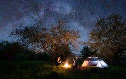 Paartoeristen die bij een kampvuur dichtbij tent onder bomen en het hoogtepunt van de nachthemel van sterren en melkachtige manie stock foto