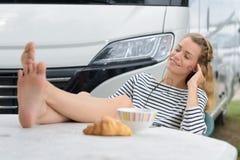 Paartouristen sitzen nahe ihrem Reisemobil, das frühstückt stockfoto