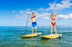 Paartribune die omhoog in Hawaï paddelen Stock Foto's
