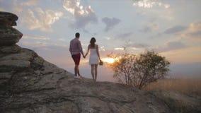 Paartribune op rots en het letten op zonsondergang bovenop de berg stock video