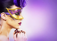 Paarty woman swearing golden mask on light backgound Royalty Free Stock Photos