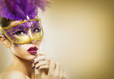 Paarty woman swearing golden mask on light backgound Stock Photography