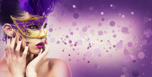 Paarty woman swearing golden mask on light backgound Stock Photo