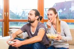Paarvideospiel und haben Popcorn Lizenzfreie Stockfotografie
