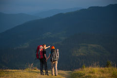 Paarwandelaars die met rugzakken handen houden, die in de bergen lopen Royalty-vrije Stock Foto