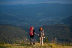Paarwandelaars die met rugzakken handen houden, die in de bergen lopen Stock Foto's