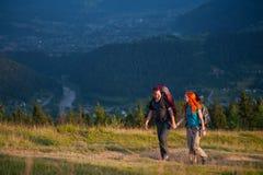 Paarwandelaars die met rugzakken handen houden, die in de bergen lopen royalty-vrije stock foto's