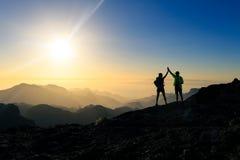 Paarwandelaars die succesconcept in bergen vieren stock foto's