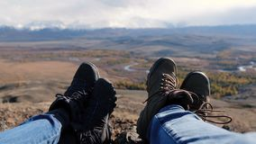 Paarwandelaars in wandelingsschoenen die op de bovenkant van moutain met verbazende mening rusten backpackers die voeten dicht om stock videobeelden