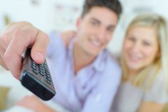 Paarzitting in bank en het letten op TV stock afbeeldingen