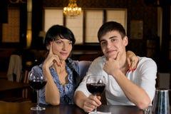 Paarzitting bij de bar die rode wijn drinkt stock fotografie