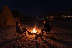 Paarzitting bij het branden van kampbrand in de nacht Het kamperen in de woestijn met wilde olifanten op achtergrond De zomeravon royalty-vrije stock fotografie