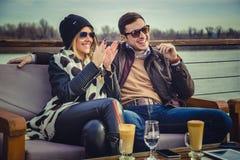 Paarzitting door de rivier en het lachen Royalty-vrije Stock Foto's