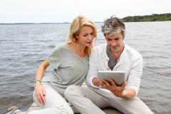 Paarzitting door het meer met tablet stock afbeeldingen