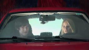 Paarzitting in een rode auto in het midden van het schoonmaken proces stock footage