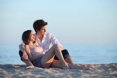 Paarzitting en het lachen op het zand van het strand bij zonsondergang royalty-vrije stock afbeelding