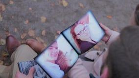 Paarzitting in het park Familie die hun zitting van het fotoalbum in het park bekijken Gelukkig paar met fotoalbum stock footage