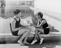 Paarzitting met hun puppy naast een pool (Alle afgeschilderde personen leven niet langer en geen landgoed bestaat Leverancierswaa Royalty-vrije Stock Foto