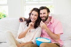 Paarzitting op bank het letten op televisie stock foto's