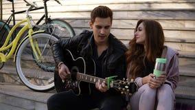Paarzitting op de de treden en het spelen gitaar Mens in zwarte toevallige het spelen gitaar terwijl het zitten met zijn meisje stock video