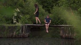 Paarzitting op een houten ponton op een rivier in zomer De echtgenoot die een digitale tablet en een vrouw gebruiken is boos en v stock videobeelden