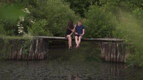 Paarzitting op een houten ponton op een rivier in zomer De echtgenoot die een digitale tablet en een vrouw gebruiken is boos over stock video