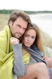 Paarzitting op het strand onder deken die, die en van ontspannen genieten Stock Foto