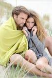Paarzitting op het strand onder deken die, die en van ontspannen genieten Royalty-vrije Stock Afbeeldingen