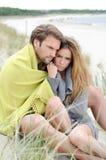 Paarzitting op het strand onder deken die, die en van ontspannen genieten Stock Afbeelding