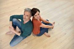 Paarzitting op houten vloer Royalty-vrije Stock Foto's
